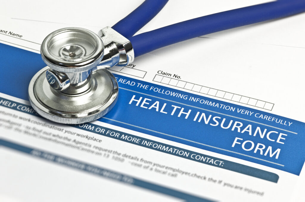 Health insurance form spread on the table with a stethoscope.