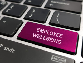 Employee wellbeing written on a laptop keyboard key.