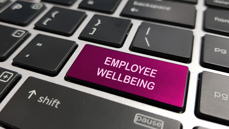 Employee wellbeing written on a laptop keyboard key.