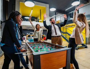 A group of diverse employees playing in an office while having a break.