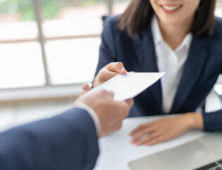 Female employee receiving employee benefits from her manager.
