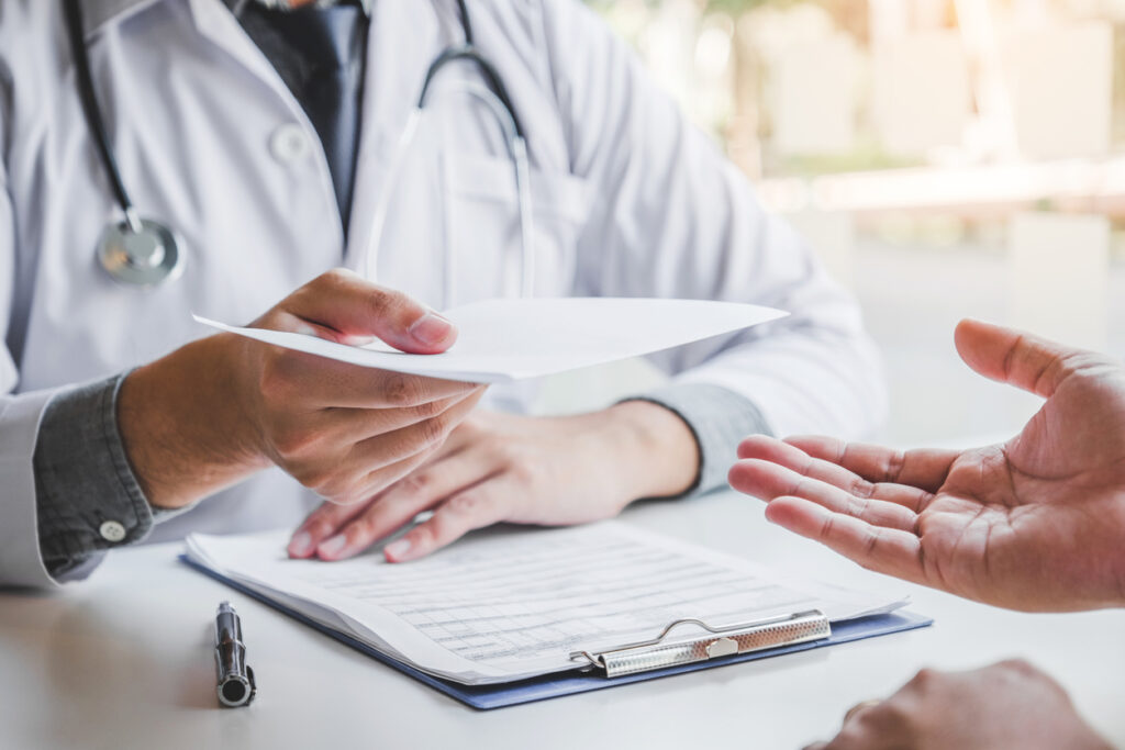 Doctor giving prescription to an employee during his check-up covered by his health plans.