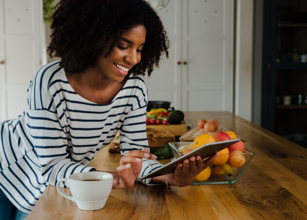 Woman having a virtual office wellness conference surrounded by fruits and healthy snacks.