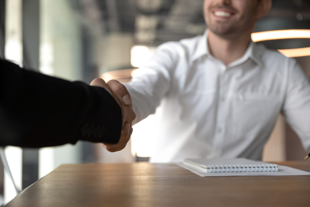 Male employee agreeing with a deal and shaking hands with his manager.