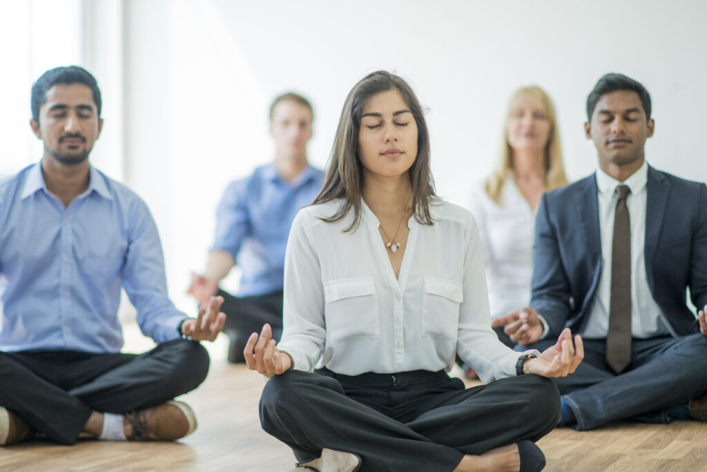 Workplace wellness programs concept, diverse group of employees meditating in the office.